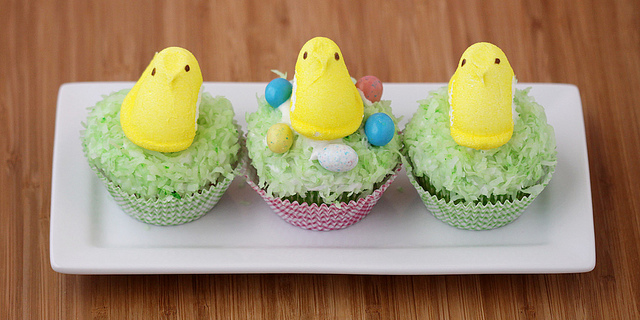 Three cupcakes on a white rectangular plate. The cupcakes are decorated with green coconut flakes and peeps. These are great alternative to traditional Easter cakes.