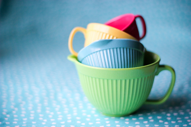 Green, blue, orange, and red measuring and cooking cups, nesting baking tools, shown on blue and white