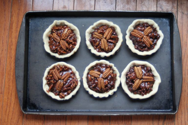 Baking Sheet shown with unbaked pecan tarts with bottom crusts in ramekins, important baking tools
