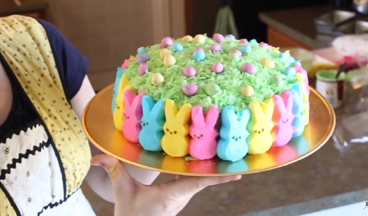 One of the prettiest Easter cakes is this one with multi-colored peeps around the sides, green coconut on top and candy eggs on the coconut.