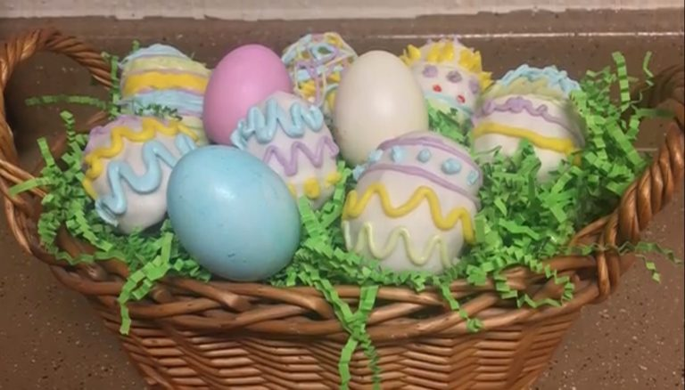 Wicker basket filled with fake grass with decorated eggs on top made with cake.