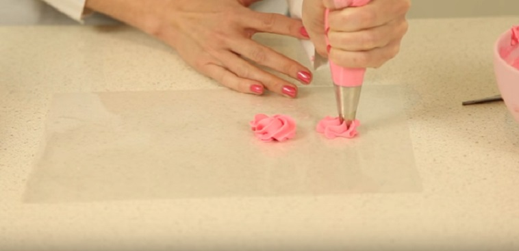 Woman making pinks roses from frosting for a baby shower cake.