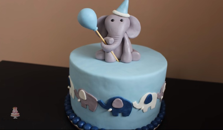 Elephant baby shower cakes are adorable. This one is a blue cake with a baby elephant on top holding a blue balloon.