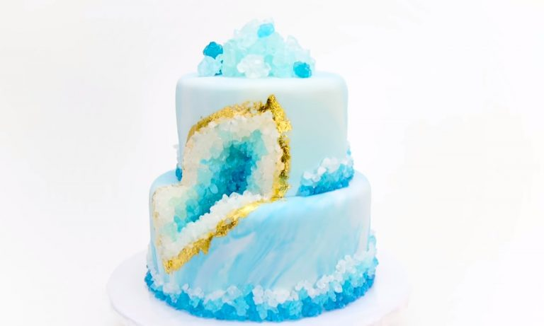Photo of blue, two layer marbled cake. The cake has a geode shape in the middle made out of rock candy. It is a beautiful option for baby shower cakes.