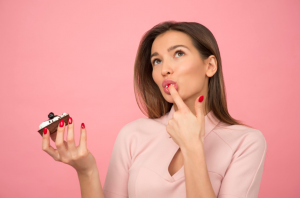 meijer cakes: woman eating-cupcake-while-standing-near-pink background inside room